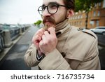 young businessman in trench... | Shutterstock . vector #716735734