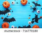 Stock photo halloween bats with pumpkins on blue wooden table 716770180