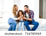 young parents sitting on the... | Shutterstock . vector #716785969