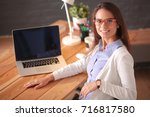 young female working sitting at ... | Shutterstock . vector #716817580