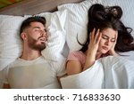 awake women in bed with snoring ... | Shutterstock . vector #716833630