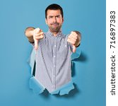 handsome man making bad signal...   Shutterstock . vector #716897383