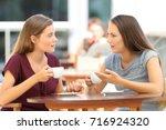 two serious friends talking... | Shutterstock . vector #716924320