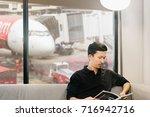 asian man reading a magazine in ... | Shutterstock . vector #716942716
