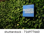 Small photo of NEW YORK CITY, USA – AUGUST 14 2015: American Express logo on display in the AMEX Centurion Lounge at New York LaGuardia Airport. A green living wall greets guests at the entrance.