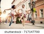 joyful couple enjoying walking... | Shutterstock . vector #717147700