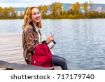 Small photo of cheerful teenage girl sitting by the river next to lies a skateboard and school backpack. school absenteeism