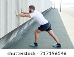 strong man stretching calf and... | Shutterstock . vector #717196546