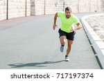 focused strong sporty man... | Shutterstock . vector #717197374