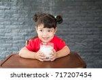 asian little girl drinking a... | Shutterstock . vector #717207454