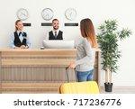 young woman near reception desk ... | Shutterstock . vector #717236776