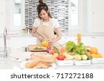young asian female slicing... | Shutterstock . vector #717272188