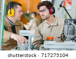 workers with earmuffs and... | Shutterstock . vector #717275104