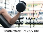 young man lift dumbbell in gym. ... | Shutterstock . vector #717277180