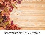 fallen leaves on wooden... | Shutterstock . vector #717279526