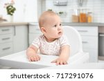 cute baby sitting in kitchen | Shutterstock . vector #717291076