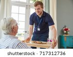 male care worker serving dinner ... | Shutterstock . vector #717312736