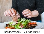 woman starts to eat medallions... | Shutterstock . vector #717354040