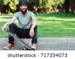 handsome smiling skateboarder... | Shutterstock . vector #717354073