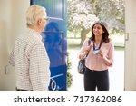 senior man opens front door to... | Shutterstock . vector #717362086
