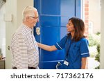 nurse on home visit greeting... | Shutterstock . vector #717362176