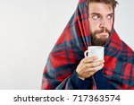 a man wrapped in a warm blanket ... | Shutterstock . vector #717363574