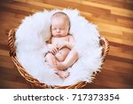 sleeping newborn baby in a wrap ... | Shutterstock . vector #717373354