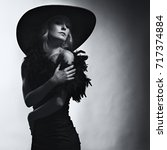 "Small photo of White woman in a black hat and a black dress in the style of ""old Hollywood"""