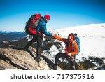 climber helping teammate climb  ... | Shutterstock . vector #717375916