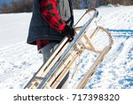 man carrying sleights up snowy... | Shutterstock . vector #717398320