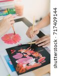Small photo of The girls help coloring the red flower with acrylic paint.