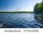 hand with spinning and reel on... | Shutterstock . vector #717411694