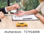 businessman giving car key over ... | Shutterstock . vector #717416008