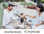 Small photo of Chic trendy couple of young hipster lovers enjoy day out on romantic date, setup in summer park, enjoying wine and delicious treats and snacks, relationship goals