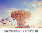 wave swinger ride against blue... | Shutterstock . vector #717434458