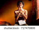 Small photo of A young man with tied up and locked with rope and hold white paper for text input in the abandoned building, Infringement hostage and the anti Human Trafficking concept.