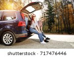 autumn trip of car and two... | Shutterstock . vector #717476446