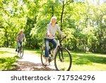 senior couple riding bikes in... | Shutterstock . vector #717524296