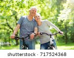 senior couple riding bikes in... | Shutterstock . vector #717524368