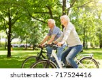 senior couple riding bikes in... | Shutterstock . vector #717524416