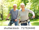 senior couple riding bikes in... | Shutterstock . vector #717524440