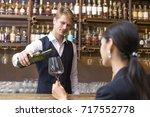 bartender serving wine to... | Shutterstock . vector #717552778