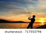 young man fishing at sunset | Shutterstock . vector #717553798