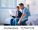 cute boy reading from printouts ... | Shutterstock . vector #717567178