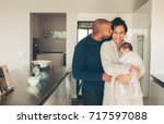 man kissing his wife holding a... | Shutterstock . vector #717597088