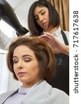 Small photo of Caucasian woman in hair salon. Hairstylist using blow dryer. Hairdressing services at affordable price.
