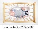 cute newborn baby in wooden bed | Shutterstock . vector #717636280