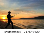 young man fishing at sunset | Shutterstock . vector #717649420