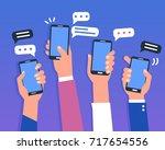 hands holding smartphones.... | Shutterstock .eps vector #717654556