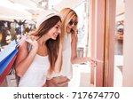 two smiling shopaholic women... | Shutterstock . vector #717674770